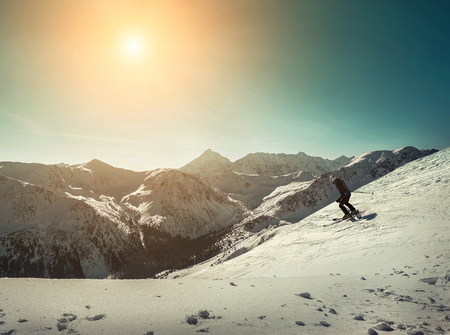 Nice mountains view at sunny day with skiers under blue sky with sun light at winter time.
