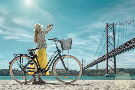 Blonde woman in summer hat and yellow skirt with her city bicycle after walking shooting near the bridge under sunlight in sunny summer day. Banco de Imagens