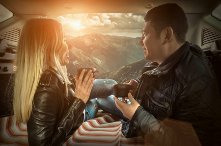 Couple in car. Blonde female and male drink tea in trunk in them car at autumn day. Stock Photo