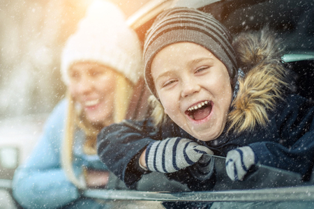 Happiness caucasian smilling boy with his mother looking out of black car window in sunny day at winter time near the forest. Stock Photo