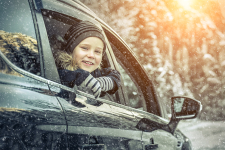 Happiness caucasian smilling boy looking out of black car window in sunny day at winter time near the forest. Stock Photo