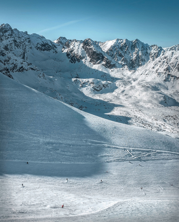Nice mountains view at sunny day with skiers under blue sky with sun light at winter time. Stock Photo - 95248326