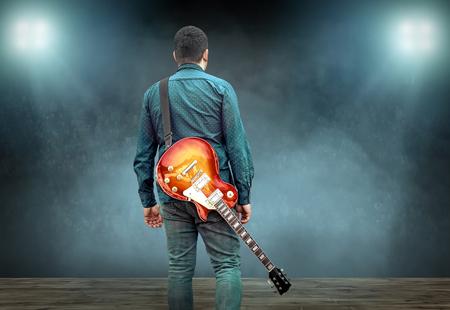 アーティストギタリストの手は、光の下で電気ギターで演奏し、演奏で練習.ソングエンターテイメントと楽器。