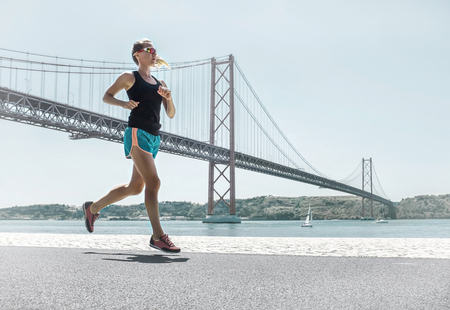 Blonde woman running training on the coastline near the Bridge under sunlight in sunny summer day. Stock fotó