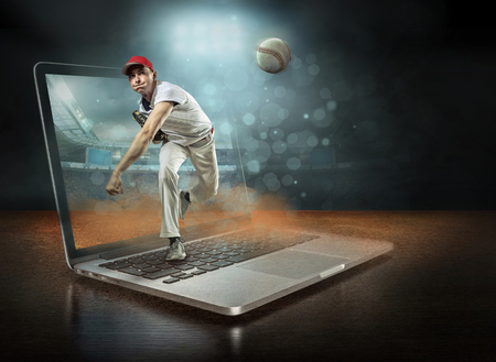 Caucassian baseball Players in dynamic action with ball in a professional sport game play on the laptop in baseball under stadium lights.