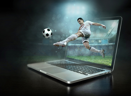 Caucassian soccer Players in dynamic action with ball in a professional sport game play on the laptop in football under stadium lights. Banco de Imagens
