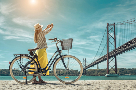 Blonde woman in summer hat and yellow skirt with her city bicycle after walking shooting near the bridge under sunlight in sunny summer day. Standard-Bild
