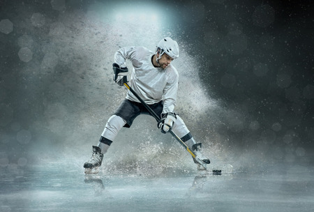 Caucassian ice hockey Players in dynamic action in a professional sport game play on the laptop in hockey under stadium lights. 写真素材
