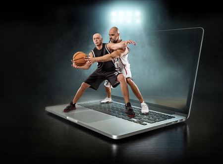 Caucassian Basketball Player in dynamic action with ball in a professional sport game play on the laptop. Stock Photo