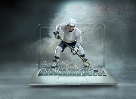 Caucassian ice hockey Players in dynamic action in a professional sport game play on the laptop in hockey under stadium lights. Banque d'images