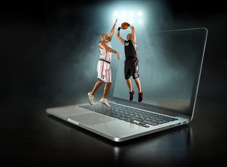 Caucassian Basketball Player in dynamic action with ball in a professional sport game play on the laptop. Standard-Bild