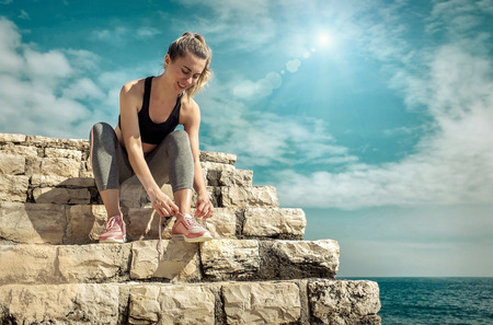 Women runner bootlace on her boot after running in sunny day under sunlight from blue sky near the sea. Stok Fotoğraf - 103544928