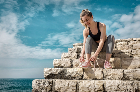 Women runner bootlace on her boot after running in sunny day under sunlight from blue sky near the sea.