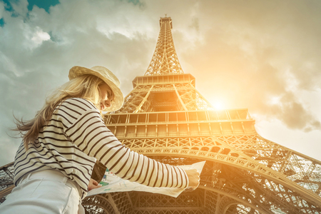 Woman tourist selfie near the Eiffel Tower in Paris under sunlight and blue sky. Famous popular touristic place in the world. Stock Photo