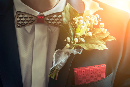Wedding white flowers on the blue mans jacket with red accessory.