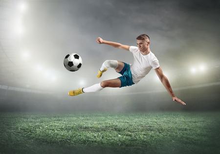 Giocatore di calcio su un campo di calcio in azione dinamica al giorno d'estate sotto il cielo con le nuvole. L'uomo sportivo sta sparando la palla all'aperto. Archivio Fotografico