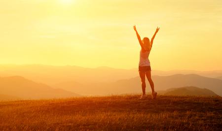 Glückliche Frau mit offenen Armen bleiben auf dem Gipfel der Bergklippenkante unter Sonnenunterganghimmel und genießen den Erfolg, die Freiheit und die glänzende Zukunft.