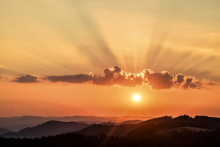 Beautfull sunset view around mountains. Sunlight on the sky with sun and cloud. Stock Photo
