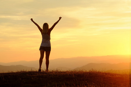 Happy woman with open arms stay on the peak of the mountain cliff edge under sunset light sky