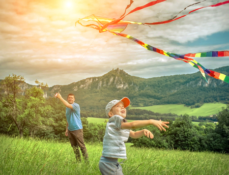 Happiness father and son launch a kite to blue sky on the field in summer sunny day. Banque d'images