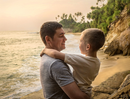 Happiness Father and son stay on the sea costline. Tropical beach under sunset sky with sun. Summer holidays.