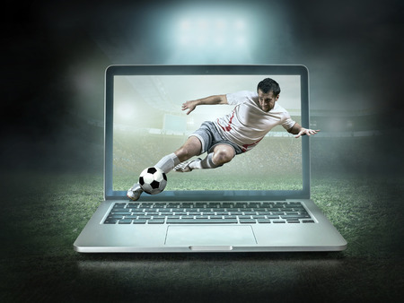 Caucassian soccer Players in dynamic action with ball in a professional sport game play on the laptop in football under stadium lights. Reklamní fotografie