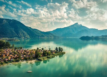 Beautiful morning sunrise view on the mountain lake in Alps under sunlight in summer. Aerial photography from a birds eye view.