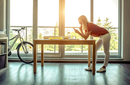 Searching for fresh ideas. Full length of young woman using computer and phone while standing in the creative office near the window in sunny day.