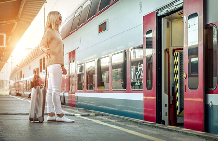 Blonde woman with her luggage stay near the red train on the peron os rail station under sun light at sunny day. Imagens