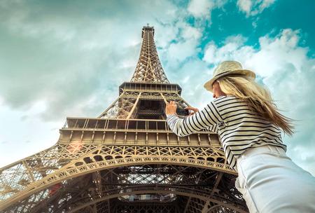Woman tourist selfie near the Eiffel Tower in Paris under sunlight and blue sky. Famous popular touristic place in the world. Reklamní fotografie