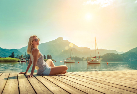 Happiness blonde woman seat on the wooden pier near the mountain lake under sunlight in morning time in summer.