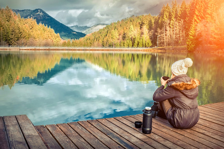Happy young woman sitting on the wooden pier and drink coffee, mountain lake beautiful view with blue sky at autumn sunny day. Reklamní fotografie