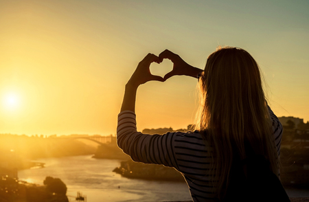 Happy blonde woman - tourist heart of hads, beautiful city view with ships on the river in sunny day under sunset sky. Reklamní fotografie
