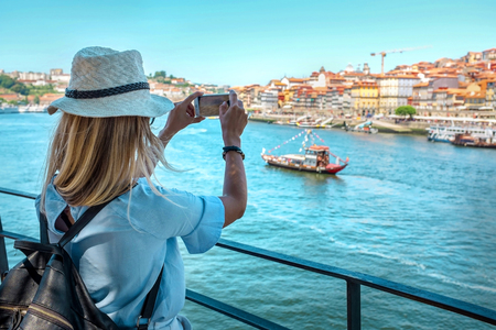 Happy blonde woman - tourist shot on her smartphone camera beautiful city view. with ships on the river in sunny day. Reklamní fotografie