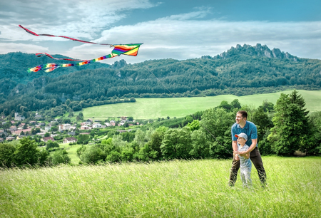 Happiness father and son launch a kite to blue sky on the field in summer sunny day. Reklamní fotografie