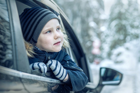 Happiness caucasian smilling boy looking out of black car window in sunny day at winter time near the forest. Reklamní fotografie