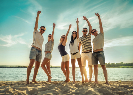 Happy Friends stay with hands up and funny on the beach under sunset sunlight in sunny day. Reklamní fotografie