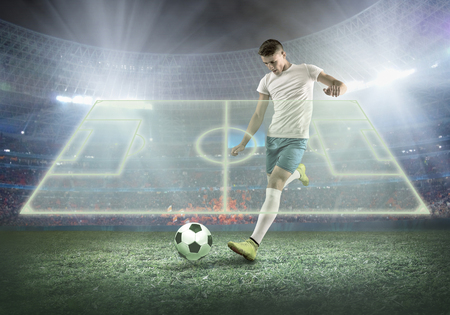 Soccer player on a football field in dynamic action at summer day under sky with clouds. Sporty man is shooting the ball outdoor.