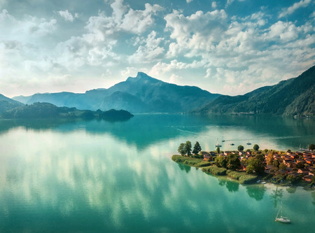 Beautiful morning sunrise view on the mountain lake in Alps under sunlight in summer. Aerial photography from a bird's eye view.