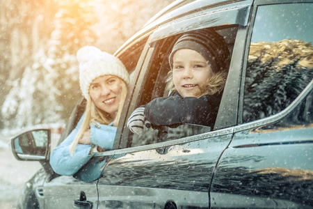 Happiness caucasian smilling boy with his mother looking out of black car window in sunny day at winter time near the forest. Standard-Bild