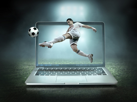 Caucassian soccer Players in dynamic action with ball in a professional sport game play on the laptop in football under stadium lights. Stock Photo