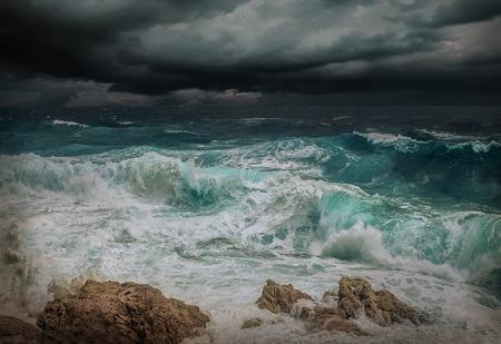 Vista mare tempestosa vicino alla costa in serata. Onde, gocce spruzzate sotto il cielo drammatico scuro.