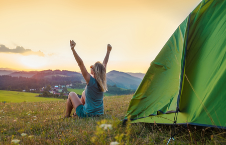 Happy woman with open arms stay near tent around mountains under sunset light sky enjoying the  leisure and freedom. Фото со стока
