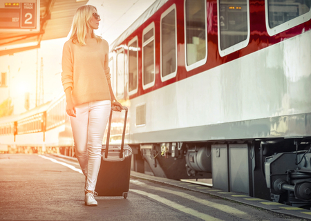 Blonde woman with her luggage go near the red train on the peron os rail station under sun light at sunny day.
