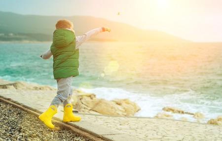 Happy childhood, little boy play near the sea on a sunny day Reklamní fotografie
