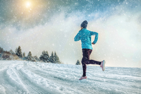 Running woman. Runner on the snow in winter sunny day. Female fitness training outdoors. Stock Photo