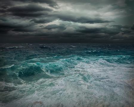 Stormachtig uitzicht op zee in de buurt van kustlijn op moment van de avond. Golven, bespat druppels onder donkere dramatische hemel. Stockfoto