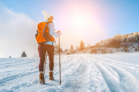 Happy woman tourist walking on the snowy trek on the peak of mountain and look on the nice winter view in sunny cold day. Concept travell and freedom. Reklamní fotografie