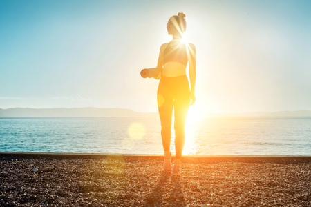 Young woman stay on the sea coastline under sun light at morming time. Yoga concept. Summer fresh air from sea. Reklamní fotografie