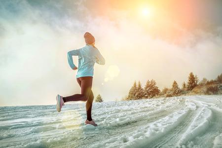 Running woman. Runner on the snow in winter sunny day. Female fitness training outdoors. Reklamní fotografie